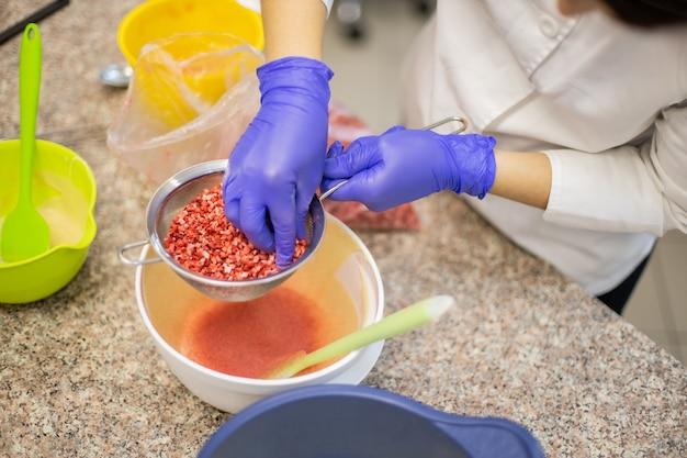 Personnel de cuisine confiant femme appliquant la poudre de baies à travers un tamis pour la décoration de tarte au chocolat