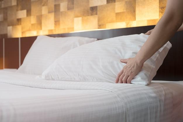 Le personnel du service d'étage de l'hôtel met en place un oreiller blanc sur le lit de l'hôtel.