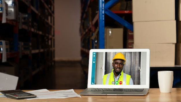 Personnel d'entrepôt parlant par appel vidéo sur un écran d'ordinateur dans un entrepôt de stockage