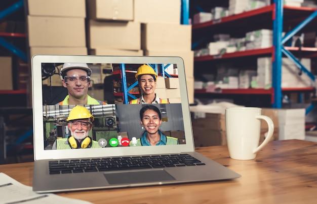 Le personnel de l'entrepôt parle sur appel vidéo à l'écran de l'ordinateur dans l'entrepôt de stockage