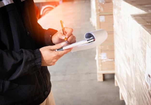 Le personnel de l'entrepôt tient un presse-papiers avec l'inventaire de la palette d'expédition.
