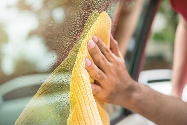 Personnel d'entretien automobile nettoie la vitre de la voiture
