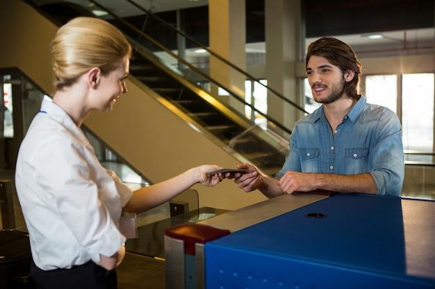 Personnel féminin donnant la carte d'embarquement au passager
