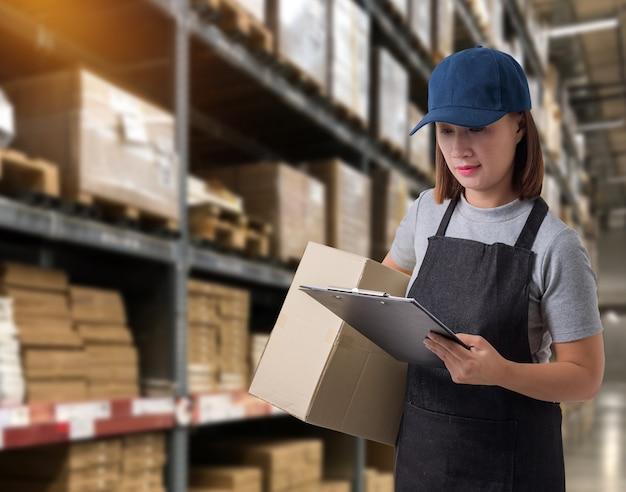 Personnel féminin livreur de produits signer la signature sur le formulaire de réception du produit avec les boîtes de colis.