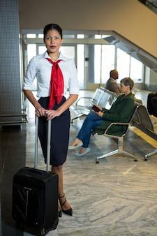 Personnel féminin avec sac à roulettes debout