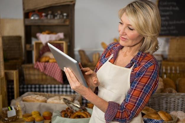 Personnel féminin souriant à l'aide de tablette numérique au comptoir