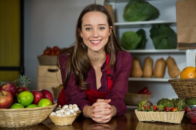 Personnel féminin souriant debout à la section biologique du marché