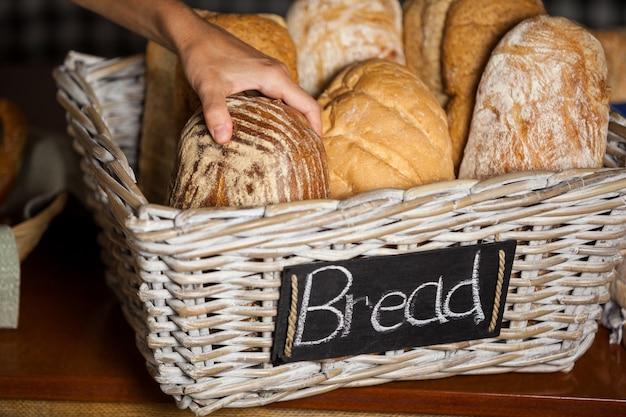 Personnel féminin tenant des pains au comptoir en boulangerie