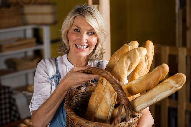 Personnel féminin tenant un panier de baguettes en boulangerie