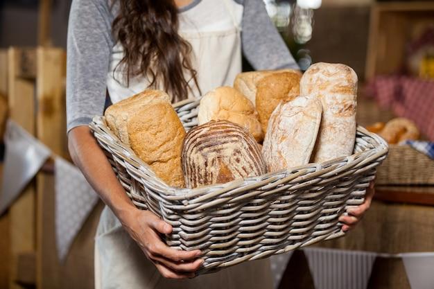 Personnel féminin tenant un panier en osier de divers pains au comptoir en boulangerie