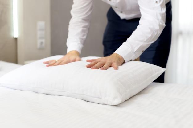 Le personnel de l'hôtel met en place un oreiller sur le lit