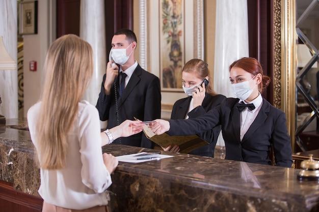 Le personnel de l'hôtel sert les clients dans des masques médicaux