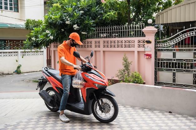 Le personnel de livraison de nourriture conduit une moto pour livrer une boulangerie au client qui commande de la nourriture en ligne