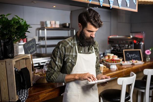 Personnel masculin à l'aide de tablette numérique au comptoir