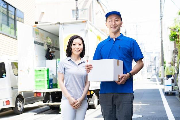 Personnel masculin asiatique transportant des bagages et des clientes à l'extérieur