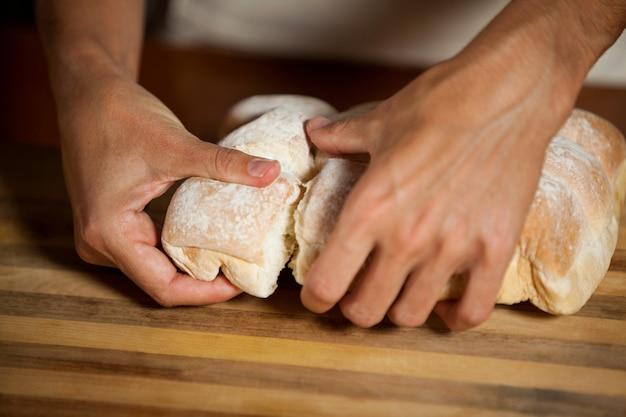 Personnel masculin déchirer un petit pain dans une boulangerie