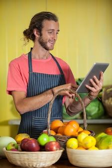 Personnel masculin souriant à l'aide de tablette numérique dans la section organique