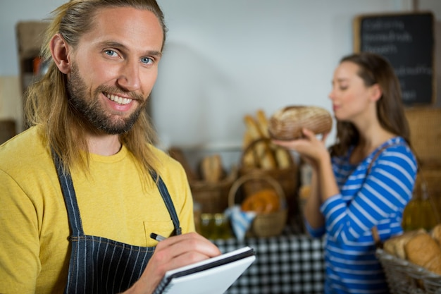 Personnel masculin souriant écrit sur le bloc-notes au comptoir