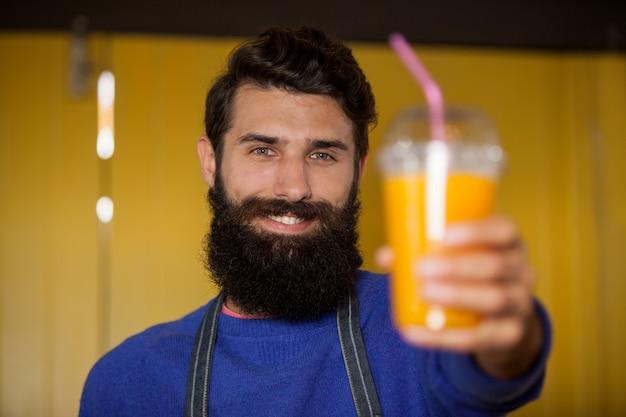 Personnel masculin tenant un verre de jus d'orange à la section biologique