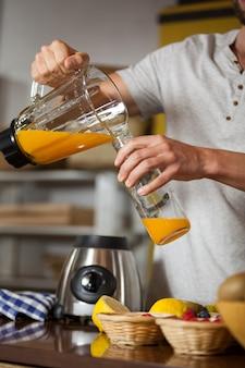 Personnel masculin, verser du jus dans une bouteille