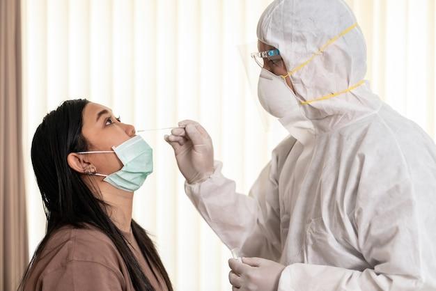 Le personnel médical avec une combinaison epi teste le coronavirus covid-19 à une femme asiatique