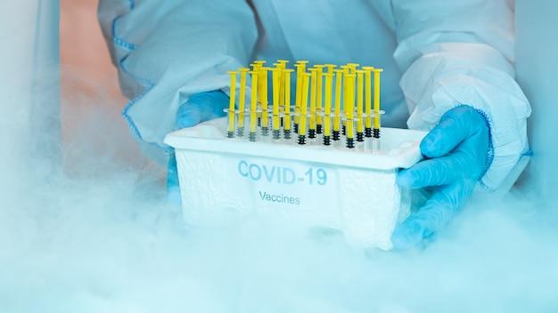 Personnel médical distribuant le plateau de vaccin covid-19 à l'intérieur du congélateur. concept de soins de santé et médical