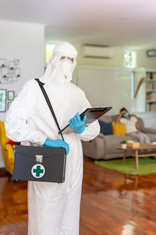 Personnel médical en équipement de protection individuelle costume epi avec fond de femme asiatique avec masque facial livraison test de coronavirus covid à la maison concept