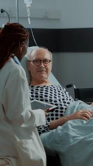 Personnel médical multiethnique et patient dans la salle d'hôpital
