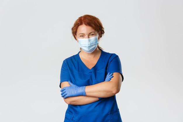 Personnel médical, pandémie de covid-19, concept de coronavirus. femme médecin, médecin ou infirmière rousse professionnelle en gommage, masque médical et gants à la poitrine confiante, bras croisés, traiter les patients.
