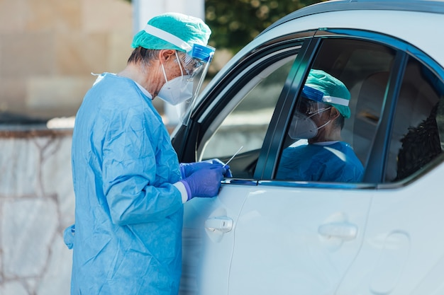 Personnel médical portant un epi, effectuant une pcr avec un écouvillon à la main, sur un patient à l'intérieur de sa voiture pour détecter s'il est infecté par le covid-19