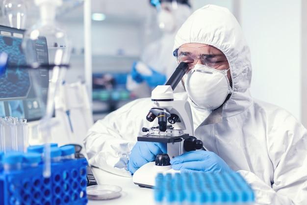 Personnel médical travaillant dans covid 19 portant un epi à l'aide d'un microscope en laboratoire. scientifique en tenue de protection assis sur le lieu de travail utilisant la technologie médicale moderne pendant l'épidémie mondiale.