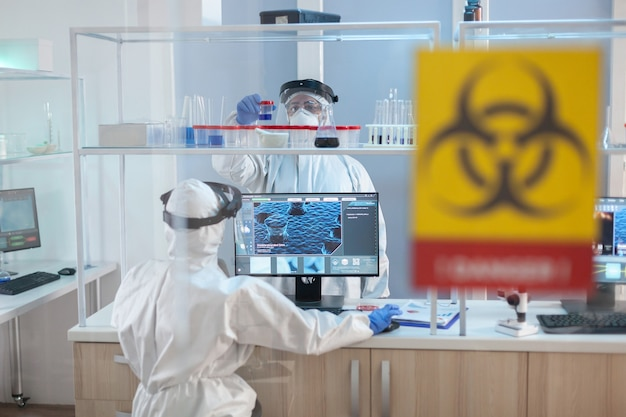 Le personnel médical travaillant dans la zone de danger de laboratoire vêtu d'un costume ppe