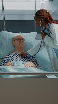 Le personnel multiethnique traite le patient dans la salle d'hôpital