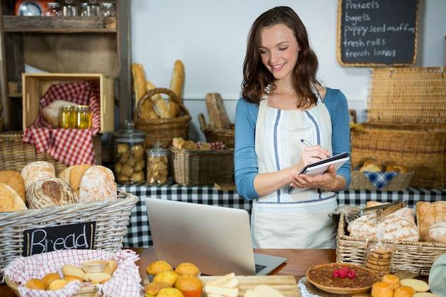 Personnel à la recherche d'un ordinateur portable tout en écrivant dans le journal au comptoir de la boulangerie