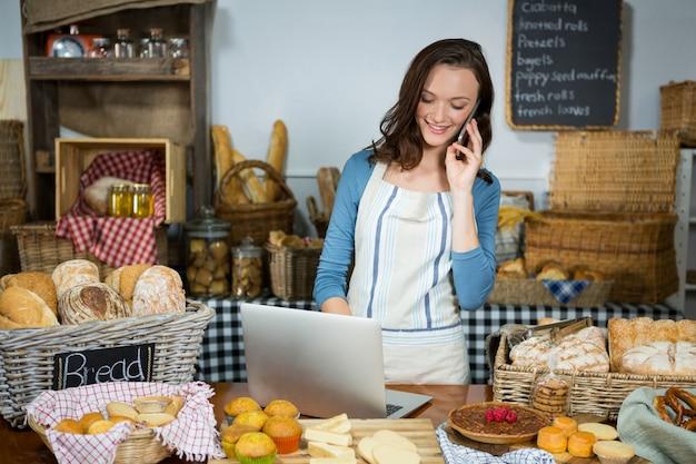 Personnel souriant à l'aide d'un ordinateur portable tout en parlant au téléphone mobile au comptoir de la boulangerie