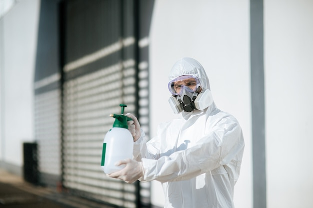 Personnel spécialisé en désinfection en tenue d'équipement de protection individuelle (epi), gants, masque et écran facial, nettoyage de la zone de quarantaine avec une bouteille de désinfectant en spray sous pression pour éliminer le covid-19