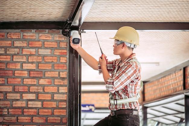 Personnel en tenue de travail vérification du système de vidéosurveillance utilisé dans le bâtiment.