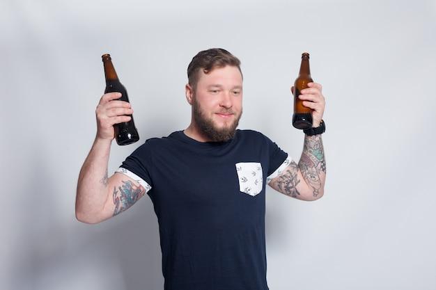 Personnes, 4k et concept de style de vie - un homme barbu brutal avec un bras tatoué boit une bière dans une bouteille. bel homme au chapeau. garçon barbu brutal avec tatouage