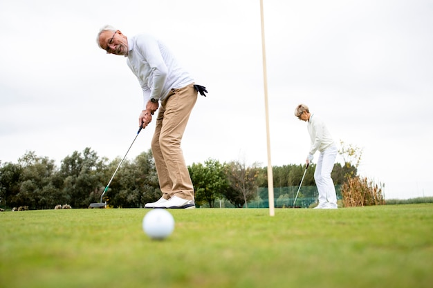 Personnes actives âgées jouant à l'or sur le terrain de golf et profitant du temps libre à l'extérieur.