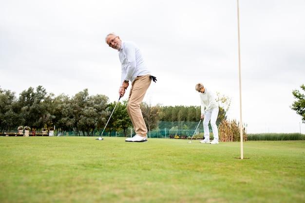 Personnes actives âgées s'amusant sur le terrain de golf et profitant du temps libre à l'extérieur.