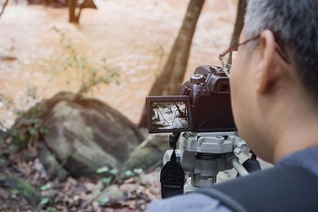 Personnes adultes un journaliste vidéo ou un journaliste prend une photo ou une vidéo au stream river fast landscape
