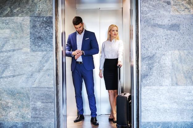 Personnes d'âge moyen debout dans l'ascenseur et monter à l'étage.