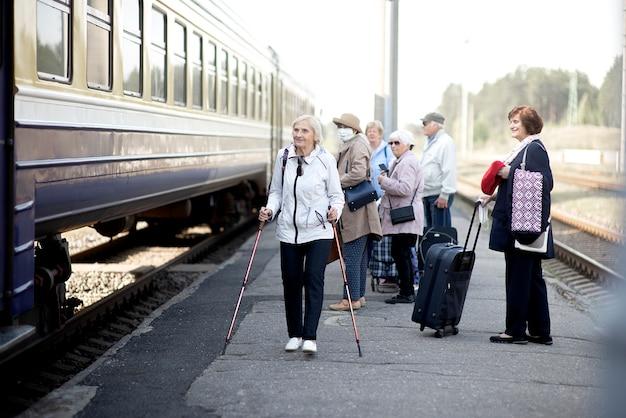 Personnes âgées âgées positives avec des masques faciaux en attente de train avant de voyager
