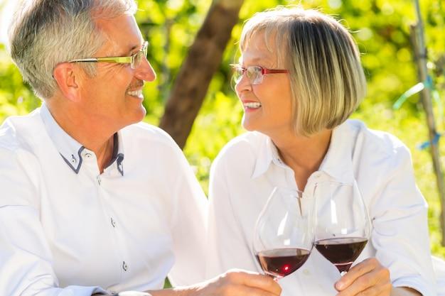 Personnes âgées assises dans un vignoble buvant du vin rouge
