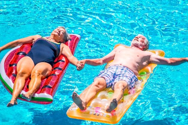Les personnes âgées couple de personnes âgées se détendent et dorment sur l'eau claire de la piscine bleue s'allongent sur des matelas gonflables colorés à la mode et se prennent la main avec amour pour un concept de vie ensemble pour toujours