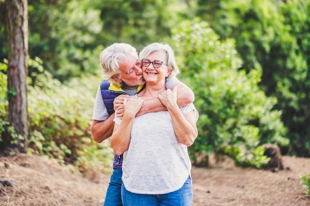 Personnes âgées avec un couple de seniors actifs caucasiens s'embrassant en relation avec la nature des plantes vertes - retraités dans les activités de loisirs en plein air - concept de bonheur pour toujours