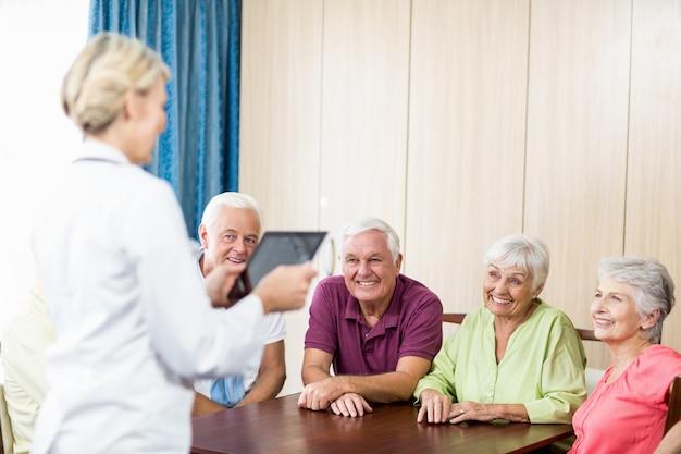 Personnes âgées écoutant une infirmière avec tablette