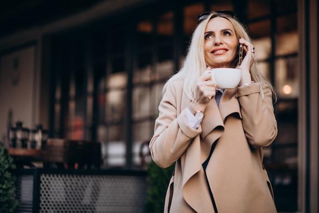 Personnes âgées femme d'affaires, boire du café à l'extérieur du café et parler au téléphone