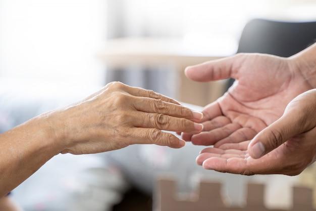 Personnes âgées femme et jeune main tenant des soins de santé