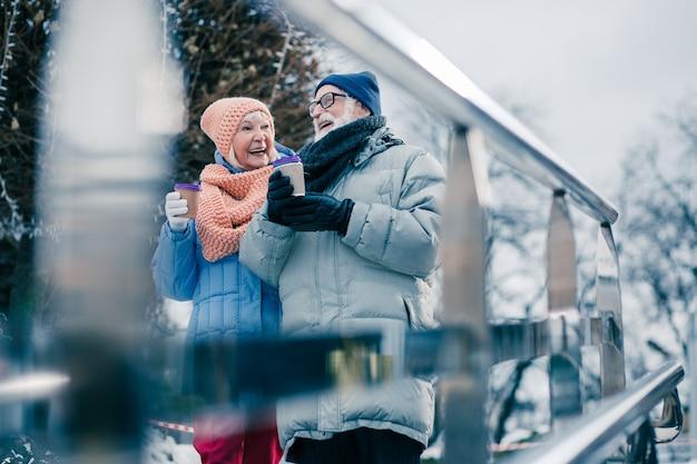 Personnes âgées gaies marchant avec du chocolat chaud dans des gobelets en papier et souriant tout en profitant de la journée d'hiver à l'extérieur